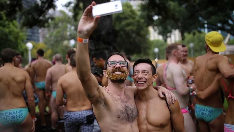 A shirtess male couple take a selfie during the annual Sydney Gay and Lesbian Mardi Gras festival in Sydney, Australia March 4, 2017.