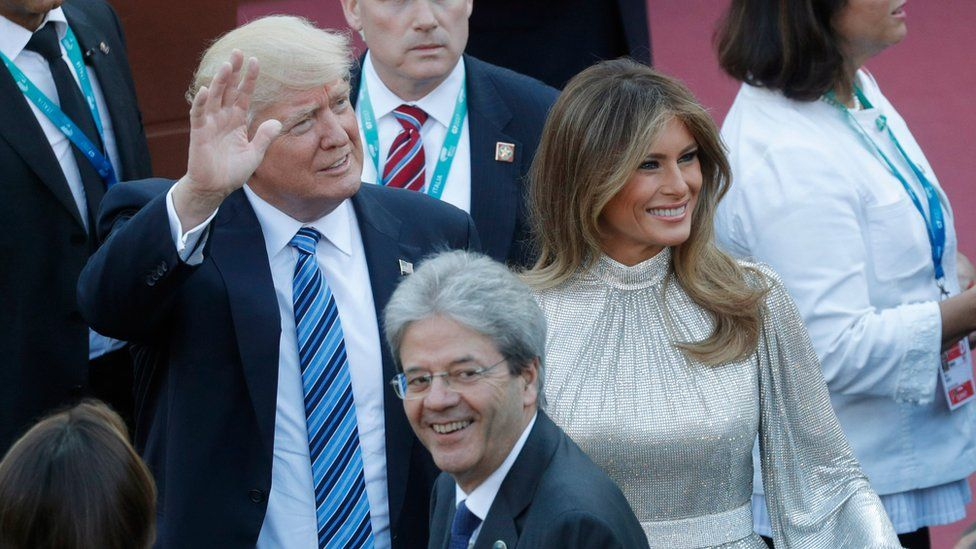 Donald Trump waves as he stands in Sicily next to his wife Melania