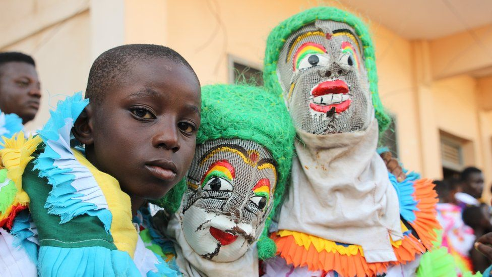 Three children pose, two of them with their faces fully covered by masks and green wigs in Sekondi Ghana
