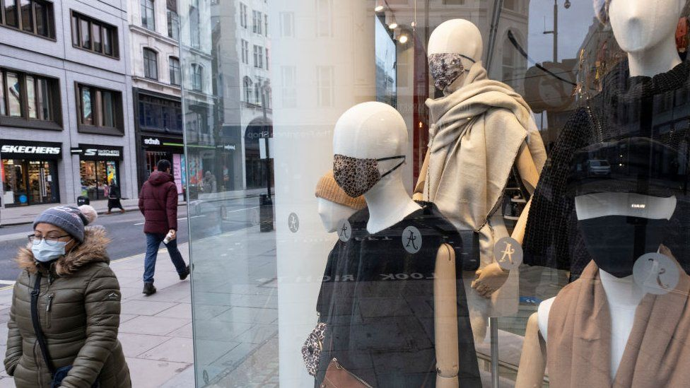 Woman walks past shop with masked dummies in window