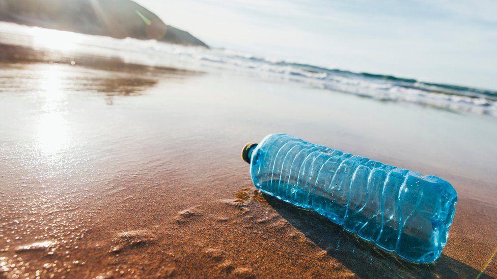 A single discarded plastic water bottle on a sandy beach