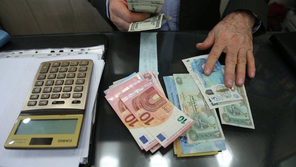 A money changer holds US dollar bills at Tehran's Grand Bazaar, Iran (14 October 2017)