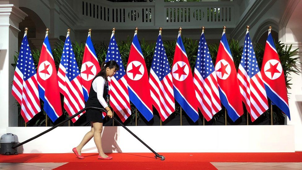 Worker vacuums spot where President Trump and Kim are expected to shake hands