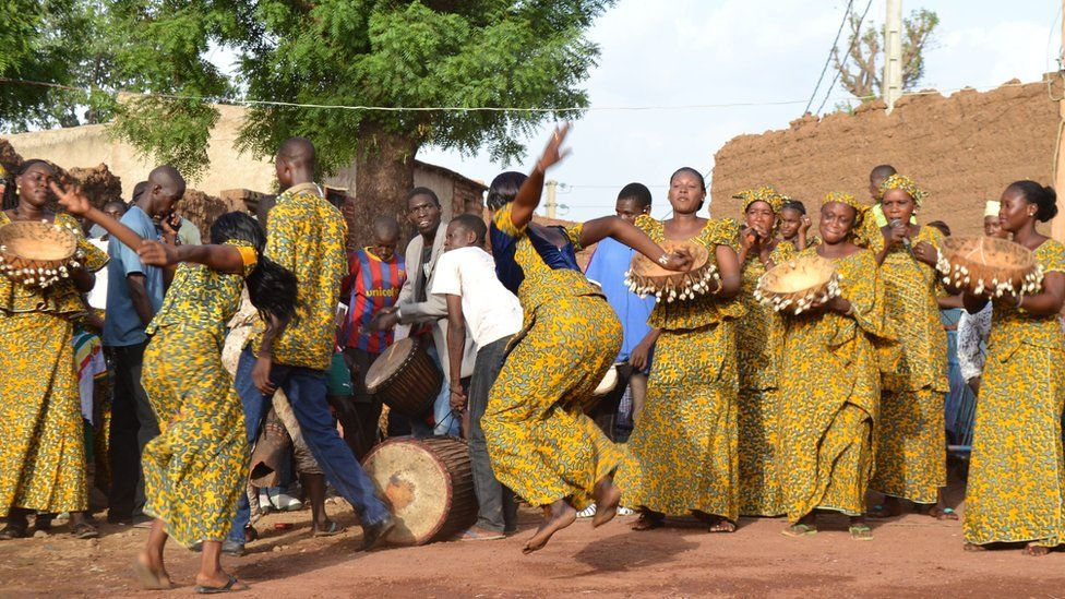 Young men and women dancing at a traditional celebration