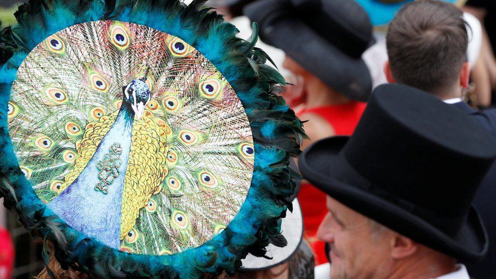 женщина на трибуне в шляпе с павлином