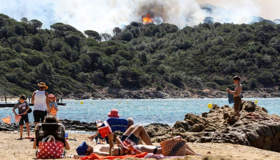 People enjoy the beach during a forest fire in La Croix-Valmer, near Saint-Tropez, on July 25, 2017 as firefighters keep on battling blazes across southern France.