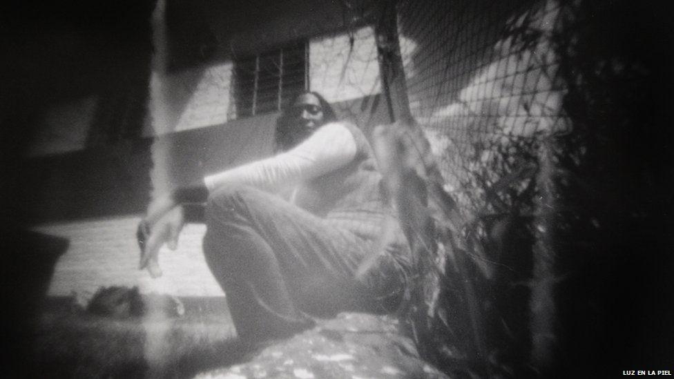 A woman leans against a fence