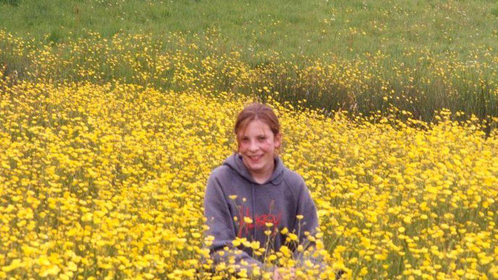 Milly standing in field of flowers