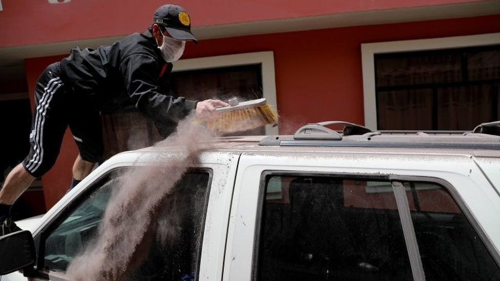 A man cleans ash from the Sangay volcano off his vehicle in the town of Alausi, in the province of Chimborazo, Ecuador, 20 September 2020