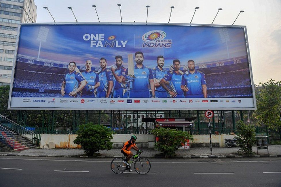 In this picture taken on October 10, 2020, a cyclist rides past a hoarding of Mumbai Indians cricketers of the Indian Premier League (IPL) cricket tournament in Mumbai.