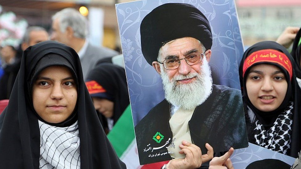 Iranian women hold posters of Iran's Supreme Leader Ayatollah Ali Khamenei durring a rally in Tehran to mark the 36th anniversary of the Islamic revolution in February 2015