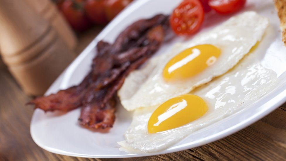 Plate of bacon, eggs and fried tomato