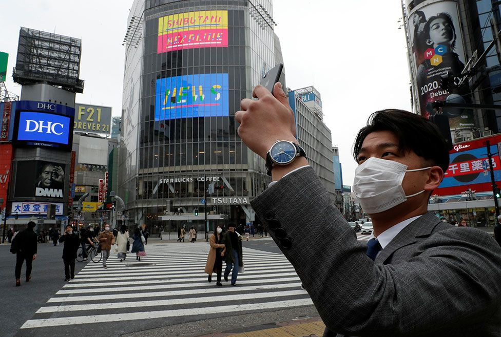 A man wearing a protective face mask takes a photo with his mobile phone at noon, at Shibuya Crossing in Tokyo, Japan