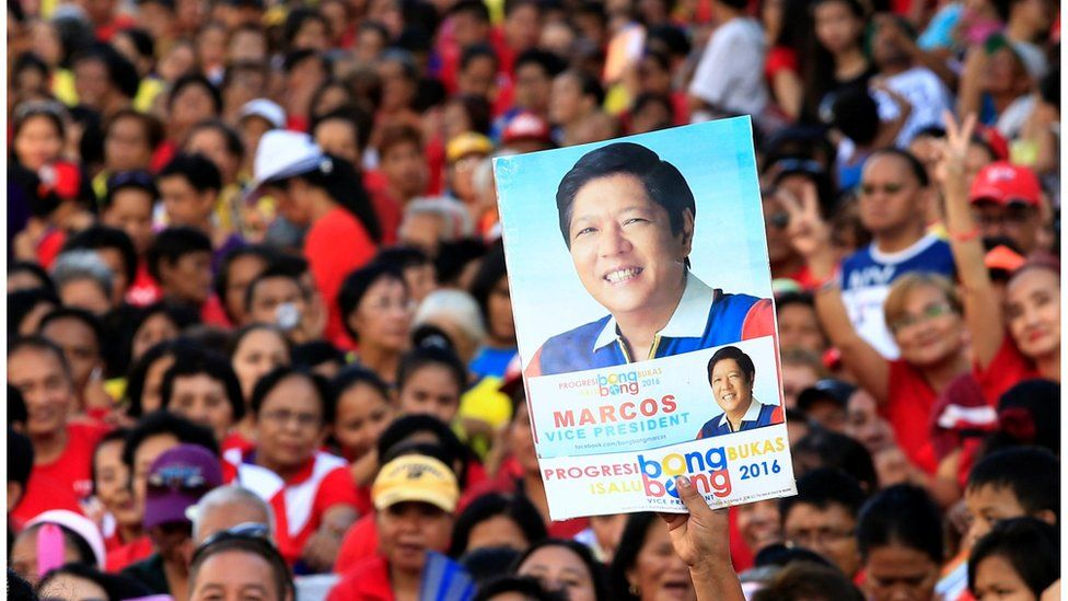 """A supporter of Philippine vice-presidential candidate senator Ferdinand """"BongBong"""" Marcos holds up a poster bearing an image of him, amid a crows at a """"rally in Metro Manila on 2 May"""