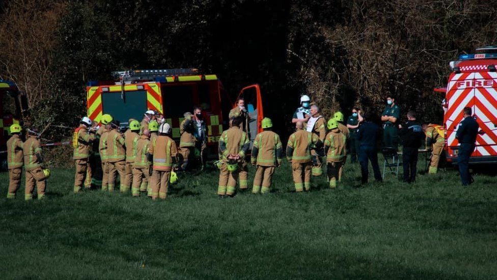 Firefighters at scene by cordon near woods