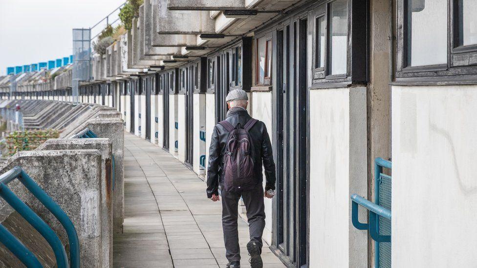 Man walking along houses in London
