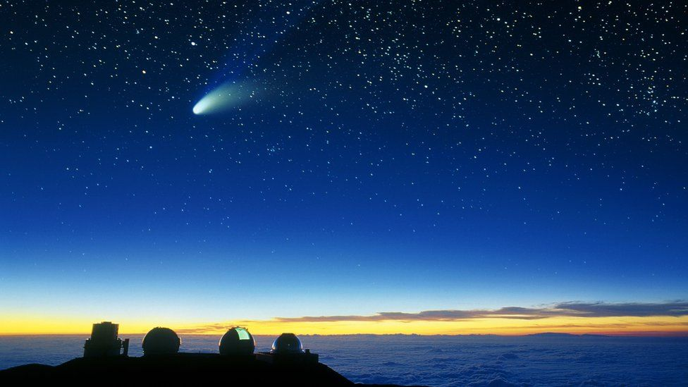 Telescope domes and a comet are seen on Mauna Lea