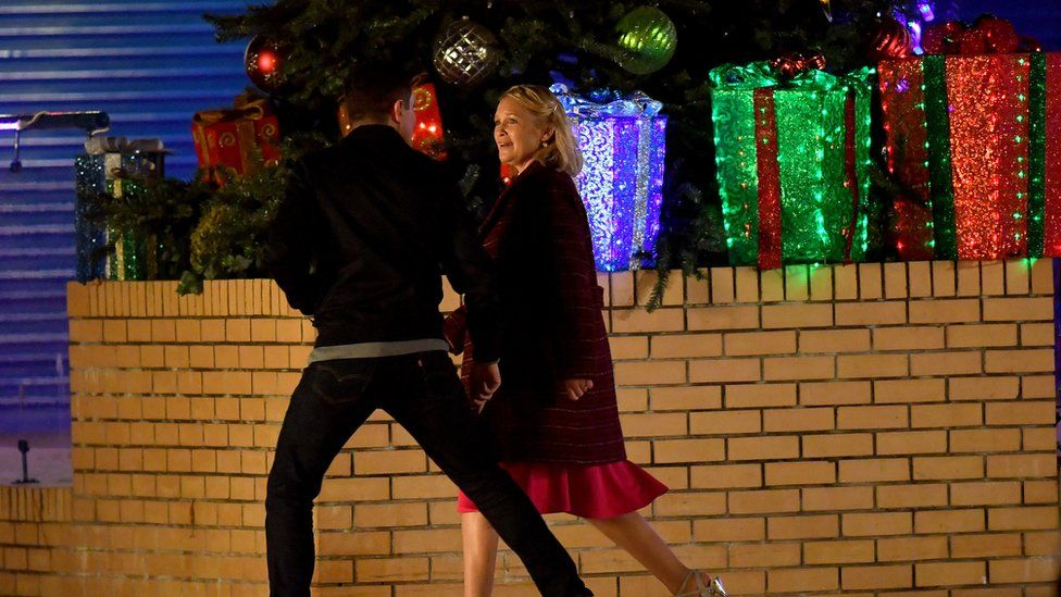 Gain and Stacey walk down a street at night and alongside a wall with Christmas decorations including presents