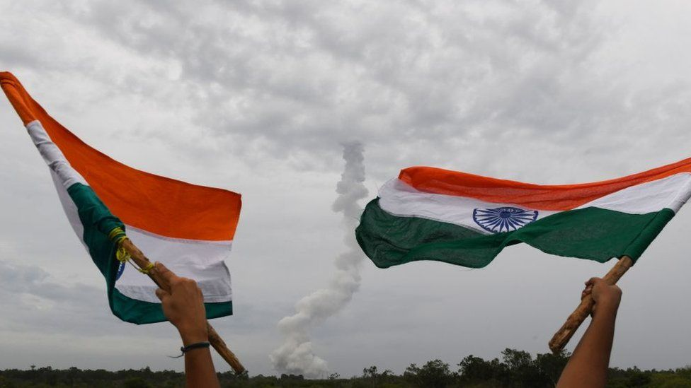 Indian residents wave Indian national flags as The Indian Space Research Organisation's (ISRO) Chandrayaan-2 (Moon Chariot 2), on board the Geosynchronous Satellite Launch Vehicle (GSLV-mark III-M1), launches in Sriharikota in the state of Andhra Pradesh on July 22, 2019
