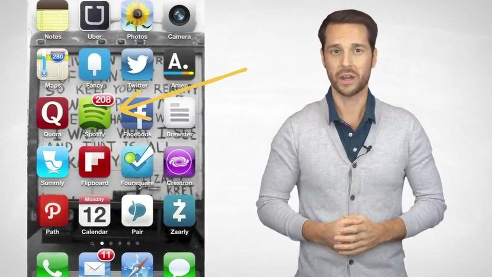A man in a cardigan addresses the camera- he is depicted next to a graphic of a mobile phone with apps on display