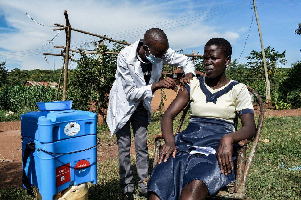 A health worker vaccinates a woman in Siaya, Kenya