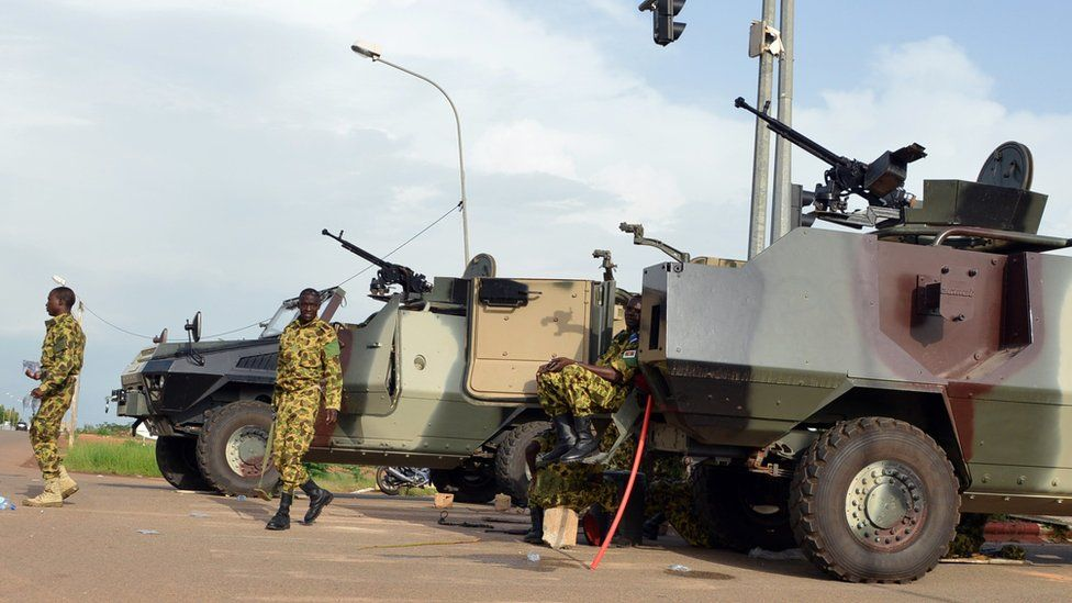 Soldiers stand next to vehicles outside the presidential palace in Ouagadougou