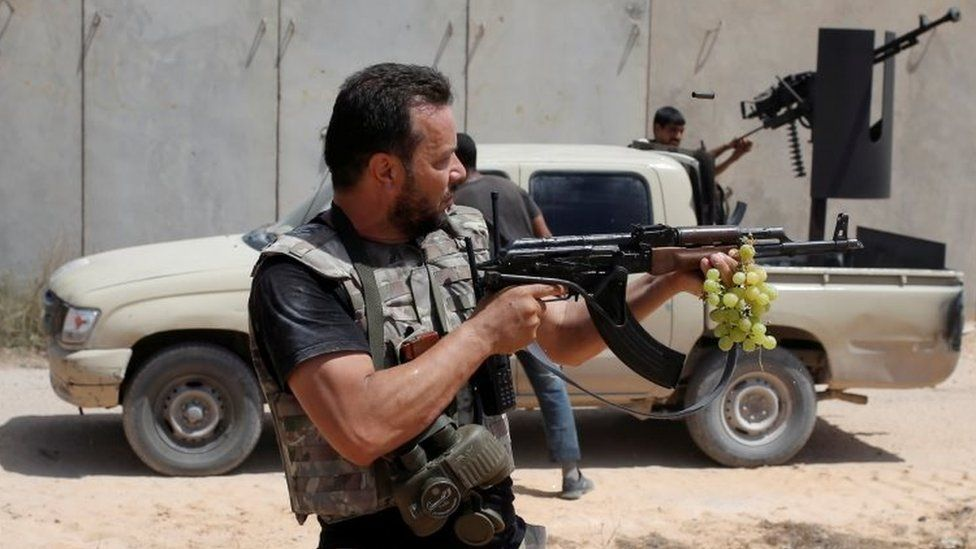 A fighter of Libyan forces allied with the UN -backed government fires a rife at Islamic State fighters during a battle in Sirte (31 July 2016)