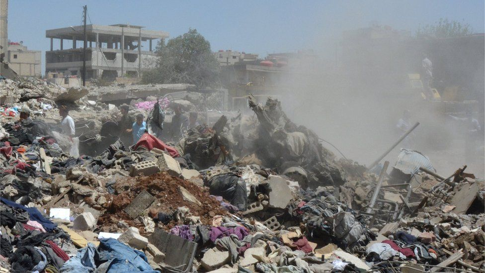 People look for survivors under debris at a damaged site in Qamishli (27 July 2016)