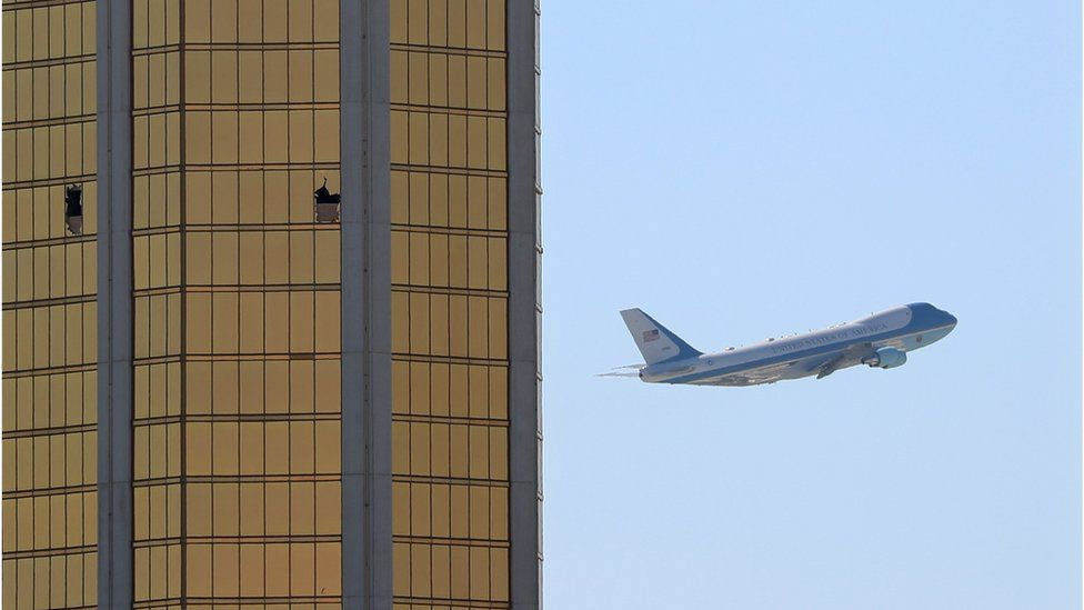 Air Force One passes to the right of the gold-coloured windows of the Mandalay hotel, two of which are shattered from the gunfire during the attack