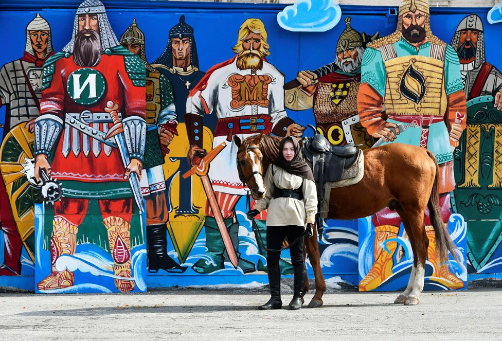 A woman stands with a horse with colourful street art depicting male warriors