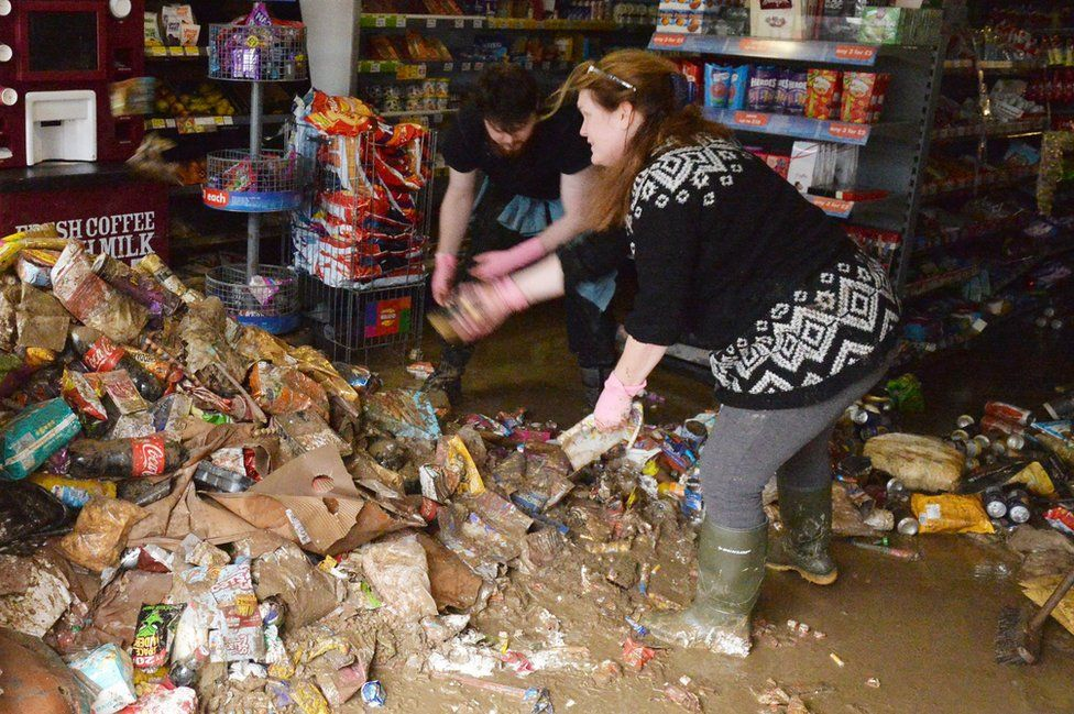 Shop workers in Cockermouth clean up the mess in the aftermath of the weekend's flooding