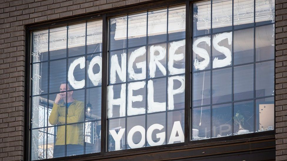 """Dave Giacomin stands by the window of his studio with the words """"Congress help yoga"""" painted on the window"""