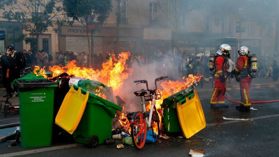 Fire-fighters stand next to bins, rubbish and a bike on fire in the Paris streets