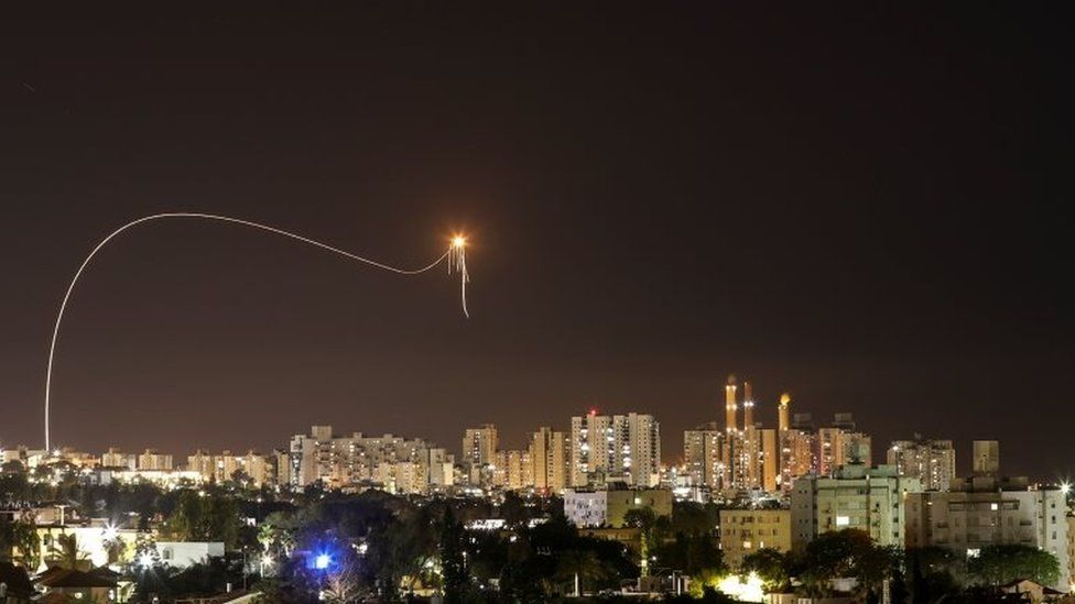 A streak of light is seen as Israel's Iron Dome intercepts rockets launched from the Gaza strip