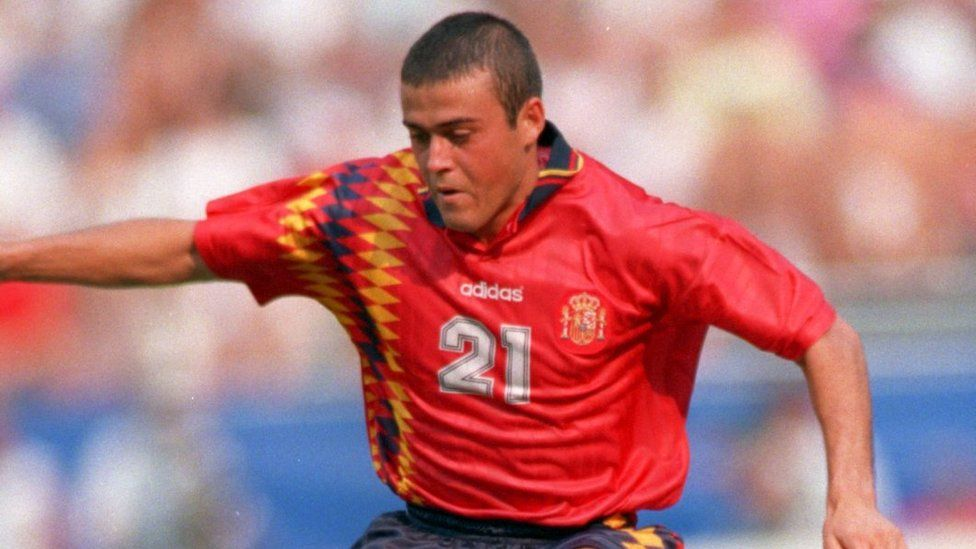 Luis Enrique concentrates on his run, arms in the airs, at the 1994 World Cup. He's wearing a red shirt, number 21, with diamonds on the right-hand side.