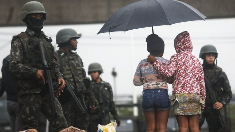 """Youngsters stand near Brazilian soldiers during a """"Mega Operation"""" conducted by the Brazilian Armed Forces along with police against gang members in seven of Rio's most violent """"favela"""" communities on August 21, 2017 in Rio de Janeiro, Brazil."""