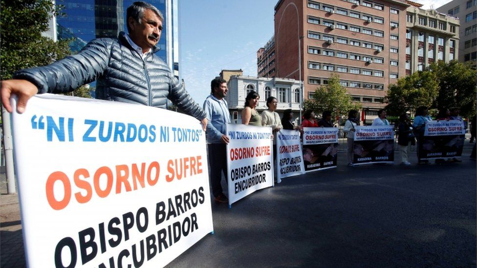 """People hold banners reading """"Neither lefties nor fools, Osorno suffers, Bishop Barros, accessory after the fact,"""" during visit"""