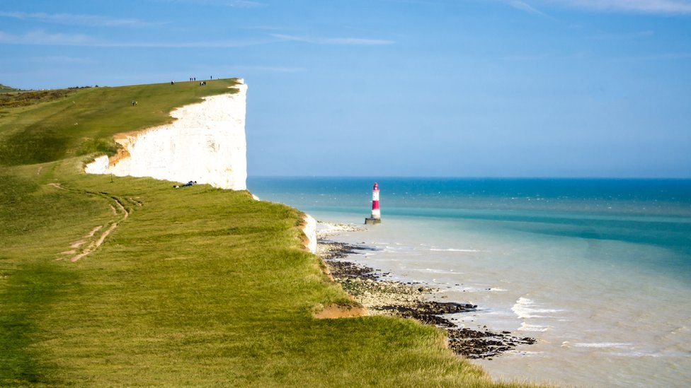 Iconic lighthouse and white chalk cliffs at Beachy Head