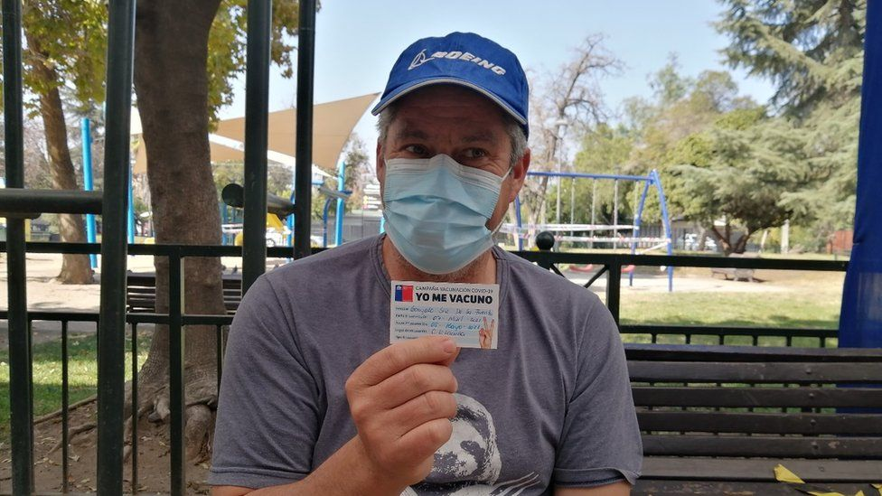 Gonzalo Sir holds up his vaccination card