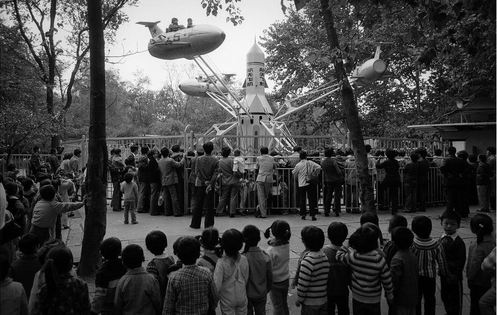 A crowd watches a ride at a fairground