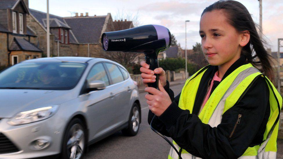 Girl using hairdryer as speed camera