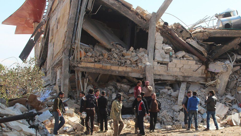 People gather around the rubble of a hospital supported by Doctors Without Borders (MSF) near Maaret al-Numan, in Syria's northern province of Idlib, on 15 Febrary 2016.