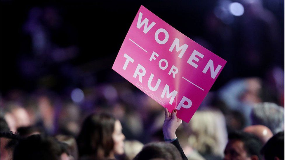 "An attendee holds up a sign in support of Republican presidential nominee Donald Trump that reads ""Women For Trump"" during the election night event in 2016"
