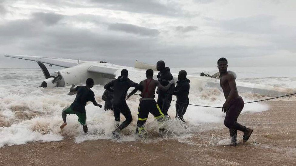 Rescuers pull the wreckage of the plane towards the shore near Abidjan, Ivory Coast, 14 October