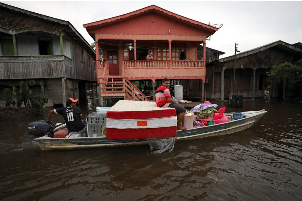 Residents take their belongings on a boat in a street flooded by the rising Solimoes river