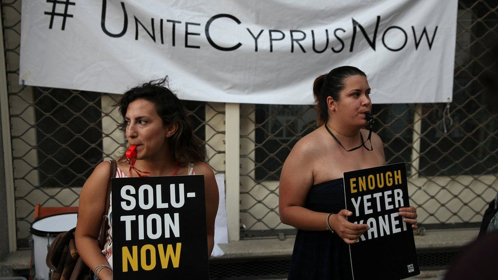 "Women with signs saying ""unite Cyprus now and ""Solution Now"""
