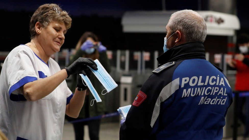 A policeman hands a mask to a commuter at Nuevos Ministerios metro station in Madrid, Spain (13 April 2020)