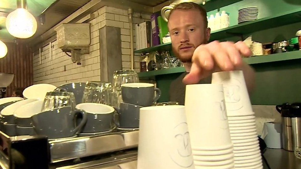 Man reaches for disposable coffee cups