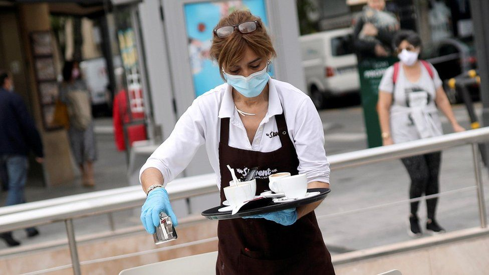 A waitress wearing a protective mask and gloves