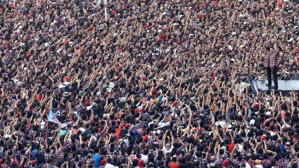 Basuki Tjahaja Purnama (right) before a big crowd of people raising their hands, at a rally in Jakarta Indonesia, February 11, 2017.